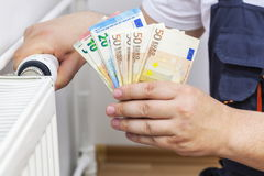 Man adjusting radiator and keep money. In background royalty free stock photo