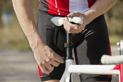 Man Adjusting Seat Of Bicycle Royalty Free Stock Photos