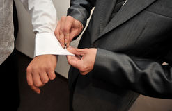 Man adjusting sleeve cuff. Hands helping adjusting sleeve buttons Royalty Free Stock Photos