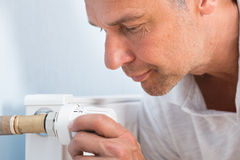 Man Adjusting Temperature Of Radiator Thermostat Royalty Free Stock Photography