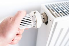 Man adjusting temperature on thermostat on radiator royalty free stock photos