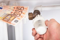 Man adjusting thermostat by euro notes Royalty Free Stock Images