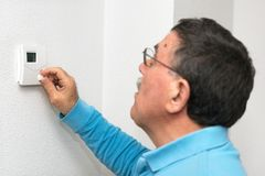 Man adjusting thermostat at home, focus on thermostat. Celsius temperature scale. Man adjusting thermostat at home, focus on thermostat. Celsius temperature stock photos