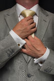 Man adjusting tie. Man in a grey suit adjusting a gold yellow tie Royalty Free Stock Photo