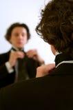 Man adjusting Tie in the mirror. A man adjusting his tie in front of the mirror Stock Photos