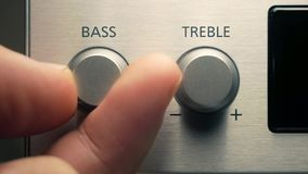 The man adjusts the bass. By turning the dimmer with his fingers