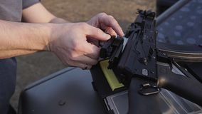 The man adjusts the collimator sight on the assault rifle. Close-up service weapons. Preparation for shooting stock video footage