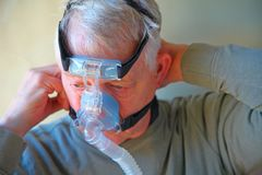 Man adjusts CPAP headgear stock images