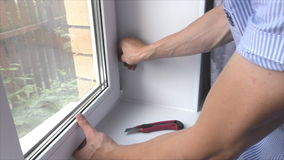 The man adjusts hinges at  window stock video footage