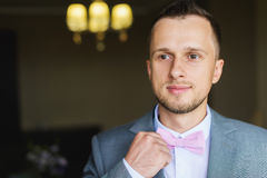Man adjusts his bow tie. Elegant young fashion man dressing up for wedding celebration. Man adjusts his bow tie Stock Photo