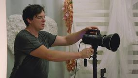 Man adjusts light device for photoshoot stock video