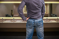 Man adjusts after peeing on the public toilet Royalty Free Stock Photos