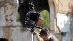 Man adjusts the retro camera among the ruins. Man adjusts the an old retro camera among the ruins stock video