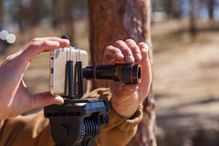 Man takes pictures on the phone with lenses. A man adjusts the smartphone on a tripod with lenses. The photographer travels taking pictures of the landscape Royalty Free Stock Image