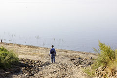 Man admires the nature. Small human stays before huge lake on th Stock Photo