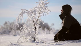 A man admires the tree in the snow. Beautiful snow-covered land, frost on the branches stock video footage