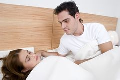 A man admiring his wife. A couple, the women is sleeping while the man is admairing the women Stock Photography
