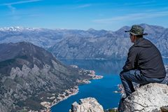 Man admiring Kotor bay from above. Tourist with a hat sitting on a large boulder and admiring the stunning landscape of the Bay of Kotor in Montenegro as seen stock image