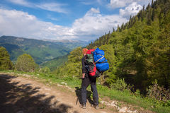 Man adventurer with big backpack goes along the mountain road Stock Image