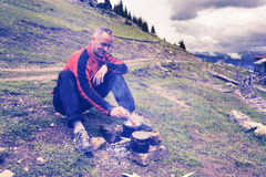 Man adventurer is cooking food on a small bonfire Stock Photos