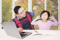 Man advising his child to learn at home. Young father advising and pointing his child for doing homework at home with a book and laptop Stock Photo