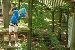 Man is afraid of heights at high rope court Stock Image