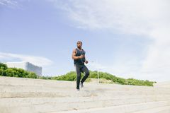 Man african running up flight of stairs, training outdoor while jogging up steps. African young man athlete steps up with energy in bleachers Royalty Free Stock Photography