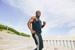 Man african running up flight of stairs, training outdoor while jogging up steps. African young man athlete steps up with energy in bleachers Royalty Free Stock Images