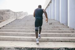 Man african running up flight of stairs, training outdoor while jogging up steps. African young man athlete steps up with energy in bleachers Stock Photo