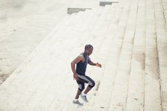 Man african running up flight of stairs, training outdoor while jogging up steps. African young man athlete steps up with energy in bleachers Stock Photos