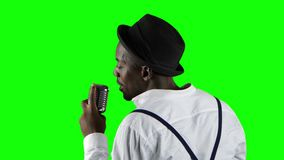 Man afrikanska amerikanen sikten från det tillbaka anseendet på mikrofonen som sjunger professionellt i en inspelningstudio lager videofilmer