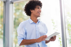 Man with afro holding digital tablet Royalty Free Stock Image