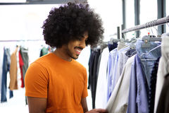 Man with afro looking for clothes in store. African man with afro looking for clothes in store Stock Photos