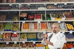 A man against the background with racks with fruits and vegetables dressed in Japanese kimono and hakama holding katana. Fruitarianism concept Royalty Free Stock Photos