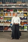 A man against the background with racks with fruits and vegetables dressed in Japanese kimono and hakama holding katana. Tarianism concept Royalty Free Stock Photography
