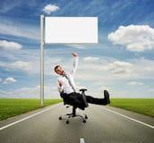 Man against empty white billboard. Happy man showing thumbs up against empty white billboard stock image