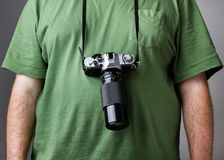 Man against gray background with camera strapped to him Royalty Free Stock Photo