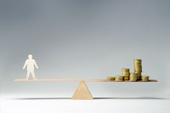 Man against money. Man balanced on seesaw over a stack of coins Stock Photo
