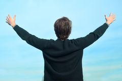 A man against the sky stands back and enjoys life. A man enjoys good weather. Man raised his hands up and laughs stock images