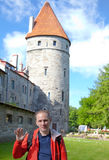 Man against towers of a city wall in Tallinn. Royalty Free Stock Photos