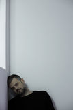 Man against a wall. Resigned sad man sitting against a white wall Stock Images