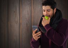 Man against wood with apple and phone. Digital composite of Man against wood with apple and phone Stock Photography