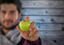 Man against wood with apple and scarf. Digital composite of Man against wood with apple and scarf Stock Photos