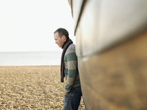 Man Against Wooden Hull Of Boat At Beach Stock Photo
