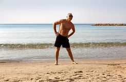 A man over 60 years engaged in gymnastics on the beach stock photography