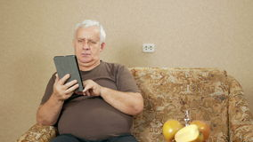 The man at the age of the tablet reads the news at home on the couch. He leafs through the finger is not interesting stock footage