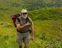 Man in age traveling. Scotland. Bearded aged man with rucksack wolking in the field Royalty Free Stock Photography