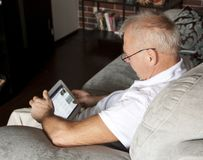 Man in age uses a digital gadget while sitting on a sofa in the interior. royalty free stock photo
