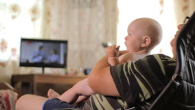 Man aged holding baby in her arms and watching TV. Baby less than a year. Home interior stock footage