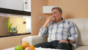 Man aged mustache resting at home and eats an apple. He looks at fish in an aquarium and fruit bites stock footage